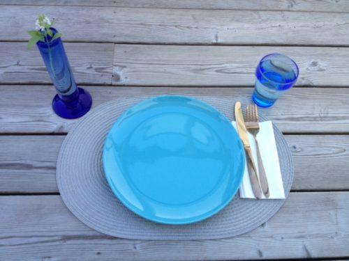 Bildet er under tittelen budsjett mat en person og viser et oppdekt bord for en person med turkis tallerken på sølvgrå bordbrikke med blått glass med vann, serviett og kniv og gaffel samt blomstervase med basilikum blomst i.