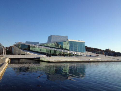 Bildet er et eksempel på et sparetips for ting å gjøre som er gratis og viser Den Norske Opera & Ballett huset i Oslo med sjøen foran og blå klar himmel i bakgrunnen.