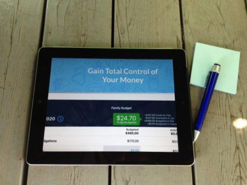 Bildet viser en budsjett app YNABpå åpnet i App Store på en iPad med en blå penn og en blå post-it blokk ved siden av seg liggende på et drivved bordflate.