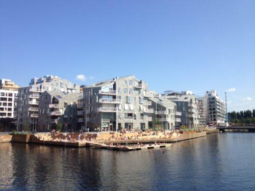 Bildet viser nye boligblokk hus i Bispevika i Oslo med Oslo Fjorden i forgrunnen en sommerdag når folk bader og visualiserer at om du har smågjeld og trenger å refinansiere det kan du bake det inn i boligen din.