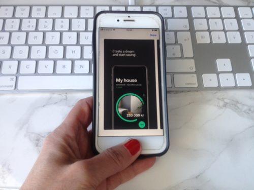 Bildet er under tittelen spare penger app på nettsiden til Låneoversikten og viser en Iphone 6G som undersøker spare appen Dreams. Iphonen blir holdt opp av en hånd over et hvitt marmorert skrivebord med et Apple keyword i bakgrunnen.