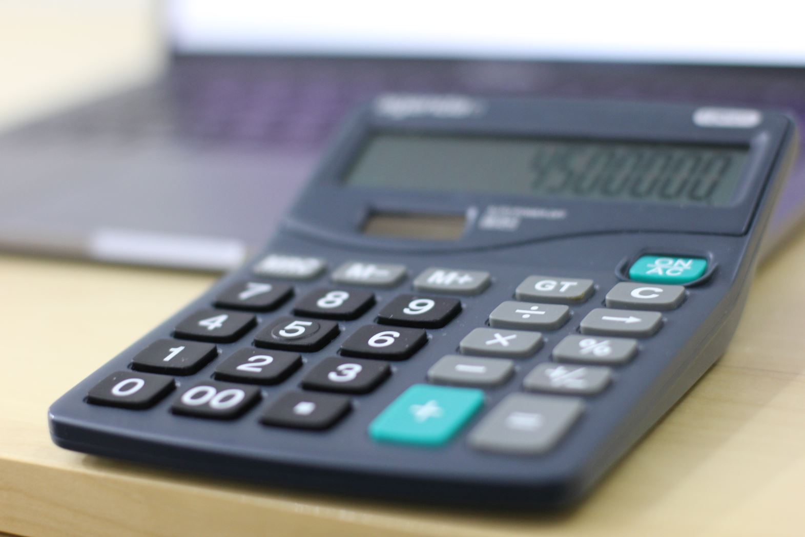 Bildet er fra siden til Låneoversikten og delartikkelen Hvem tilbyr å refinansiere boliglån med betalingsanmerkning og viser en kalkulator i forgrunnen hvor det er skrevet inn 4 og en halv million og i bakgrunnen skimter du en MacBook Pro