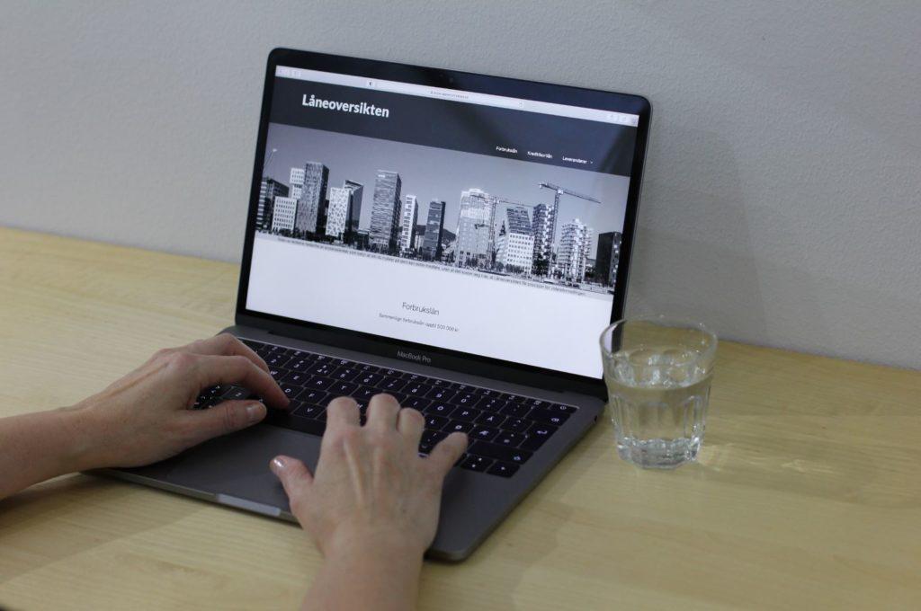 Bildet er fra Låneoversikten og kapitlet om Hvordan vet jeg om jeg har betalingsanmerkning og viser to hender på MacBook Air som ligger på et bord med et glass vann.