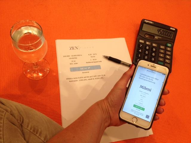 Kvinne som sitter på en orange yogamatte med utskrift fra Zen Finans, kalkulator og et glass kaldt vann mens hun holder på med mobilen sin og sjekker refinansiering hos Mileni på Låneoversikten