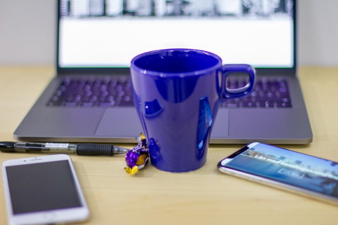 Sammenlign forbrukslån illustrert med jobbing ved PC'en med to telefoner og blå kaffikopp.